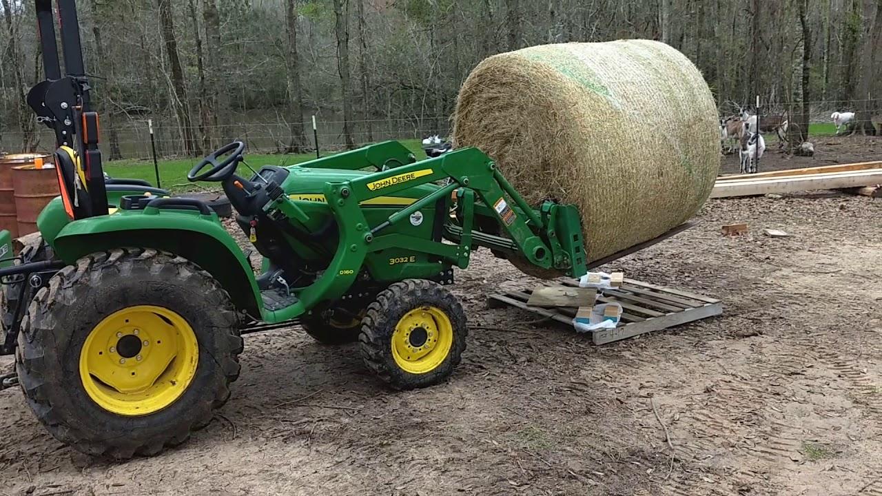 John Deere 3032E handling a round bale of hay