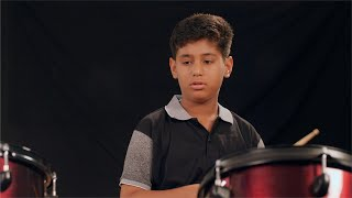 Young Indian teenage boy enjoys playing drums