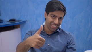 Portrait of happy Indian man giving thumbs up and smiling in dentist / doctor studio