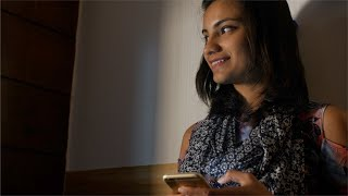 Beautiful Indian girl waving and typing on phone while sitting in her dark office cabin