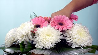 Woman hands making a bouquet of pink and white flowers - blue background