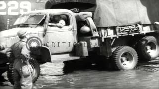 US troops disembark from a Landing Ship Medium and unload trucks and ambulances a...HD Stock Footage