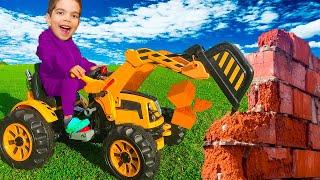 Малыш катается на мотоцикле и играет с большим трактором