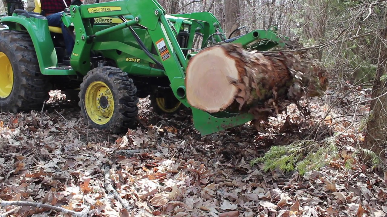 Tractor And Grapple Hauling A Log Back To The Mill Pile
