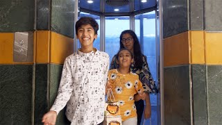 Young cheerful sibling stepping out from a mall's elevator with their shopping bags