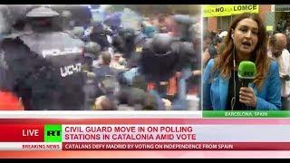 Police break down doors as officers raid polling stations in Catalonia