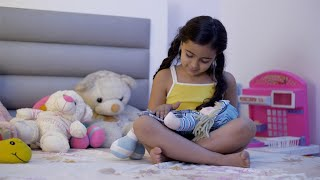 Cute little Indian girl with curly hairs playing in the bedroom - seated with a toy doll