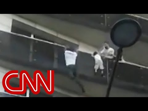 Man scales building to save dangling child
