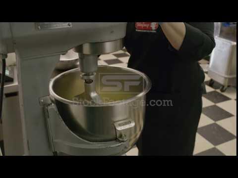 Medium shot of woman placing butter in bakery mixer