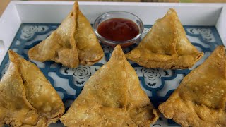 Crispy and spicy samosas plated in a serving tray with tomato sauce in India