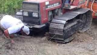 Trattore a cingoli slitta con carro di legna dal bosco.Trattore al lavoro scava buca nel terreno