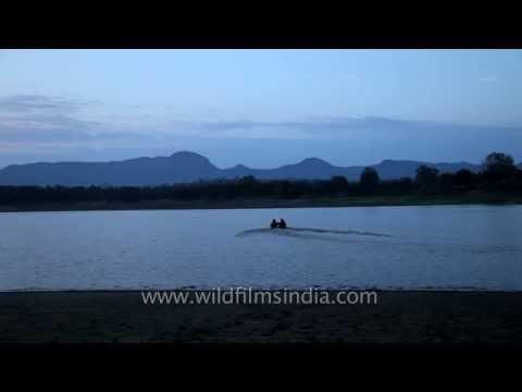 Visitors in motorboat sailing over Denwa River