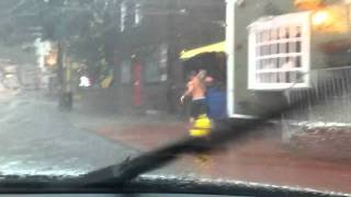 Guy Running With His Dog Over His Shoulder To Get Out Of The Rain
