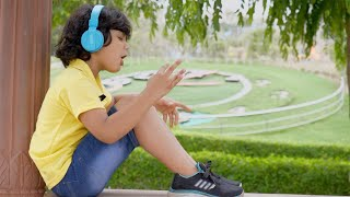 Cute little boy enjoying music using his Bluetooth headphones - technology concept