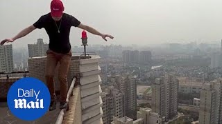 Stuntman performs tricks on shanghai skyscraper