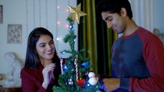 Happy Indian girl decorating Christmas tree with her cute boyfriend during Christmas