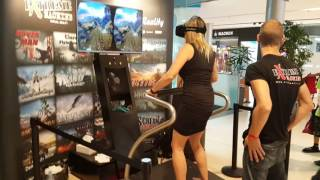 My pretty girlfriend screams hysterically on VR BMX Canyon Xtrematic simulator in shopping mall.