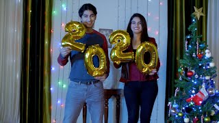 A young attractive couple dancing with golden 2020 ballons - Christmas / New Year time