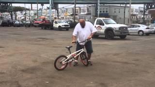 Big guy doing tricks on bike.