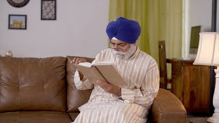 Old Sikh man wearing blue turban reading book in his living room beside a lamp - Retired life