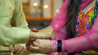 Closeup shot of a sister tying rakhi on her brother's wrist - Indian festival Raksha Bandhan