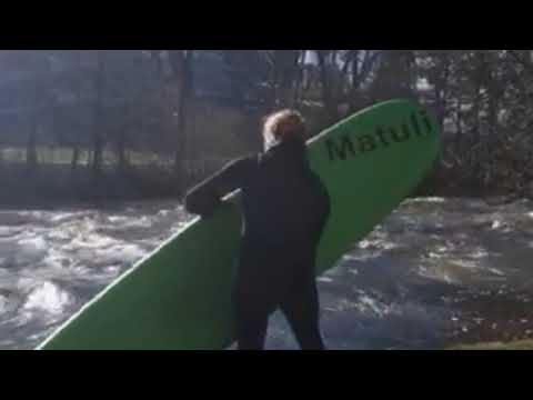 Surfing on the Red Cedar River in front of Spartan Stadium