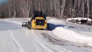 New Holland L230 Skid Steer with blade plowing through snow