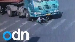 Cyclist cheats death after being run over by 14-wheel truck