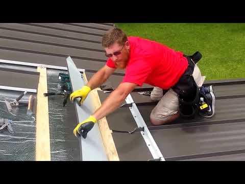 Standing seam roof installation over shingles.