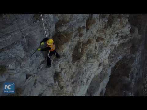 Cliff climbers clear loose rocks for railway safety