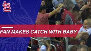 Cards fan hauls in ball while holding baby
