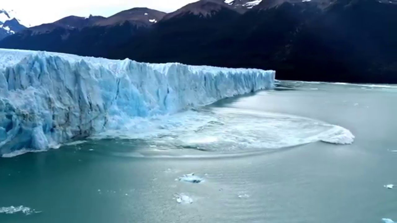 massive wall of ice falls from glacier causing a tsunami like wave