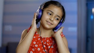 Cheerful child girl listening to music with headphones at home