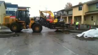 Трактор перевозит экскаватора