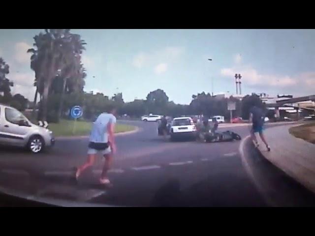 Un motorista queda atrapado bajo un coche y los viandantes lo levantan para rescatarlo