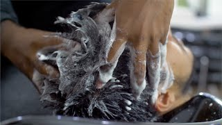 A man getting his hair washed with shampoo at a salon