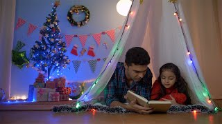 Happy Indian father reading a storybook to her daughter at night - Christmas fun