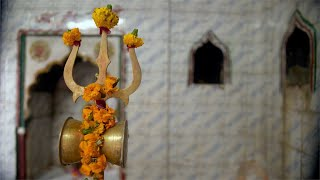 Lord Shiva's damaru tied with flowers to his Trishul made of Metal