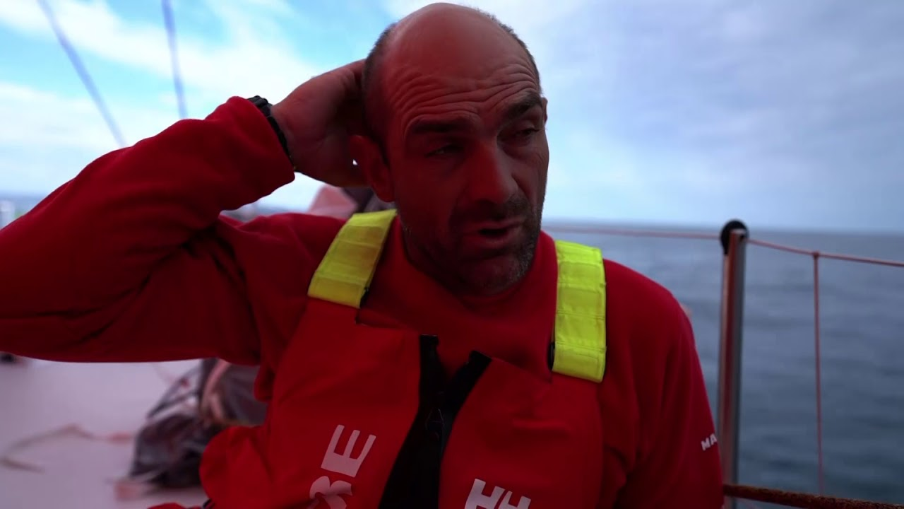 Sophie, on the bow in light conditions, talks about the compression that's happening. Knew it was coming, but it's super good to see the other boats. She points out Vestas and Dongfeng in front of them. Xabi, on the bow, talks in Spanish. He talks about Dongfeng ahead of them, and points out Vestas on the port beam. He repeats in English. 600 miles to go to Cardiff. He talks more in Spanish, repeats in English. After this leg hasn't gone well for them, this light spot is important to try to make a change. Hopefully they will be close and have more options south of Ireland. Making numbers all the time and they don't look very good for us right now. Dongfeng ahead, and have a boat between us. Going to be a big fight all the way to The Hague. Neti trims and talks in Spanish. Slomo shots of crew in the cockpit. Rob throws a coiled line. Sophie on the bow. Blair looks through binoculars for another boat. Xabi trimming. Vestas on the horizon. Dongfeng on the horizon. Crew on the bow.