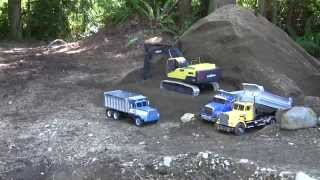 Autocar and Hayes dump trucks hauling, dumping and being loaded