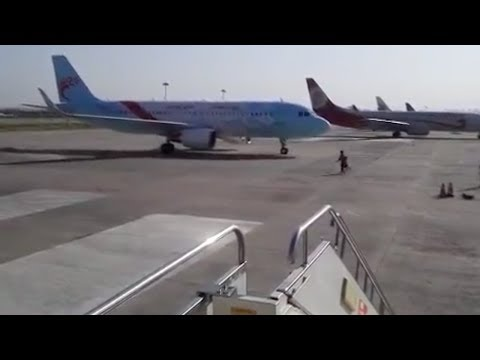 Airport ground staff stops moving aircraft
