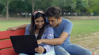 Young college couple having fun while sitting together in the campus - leisure time