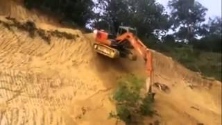 Экскаватор спускается по совершенно отвесному склону