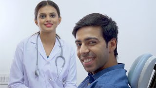 Portrait of a happy male client in the hospital and young dentist / doctor smiling