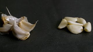 Pan shot of garlic cloves on a black background