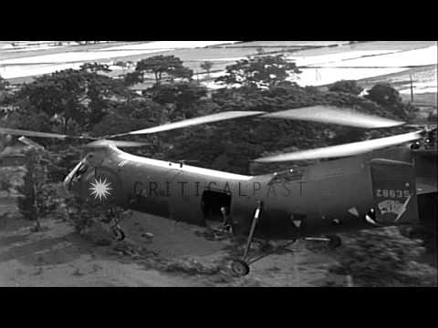 CH-21 helicopter flies over rice paddy fields in Vietnam HD Stock Footage