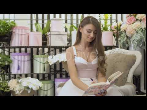 Beautiful Girl in White Dress Writes in Notebook Sitting in Vintage Chair | Stock Footage -