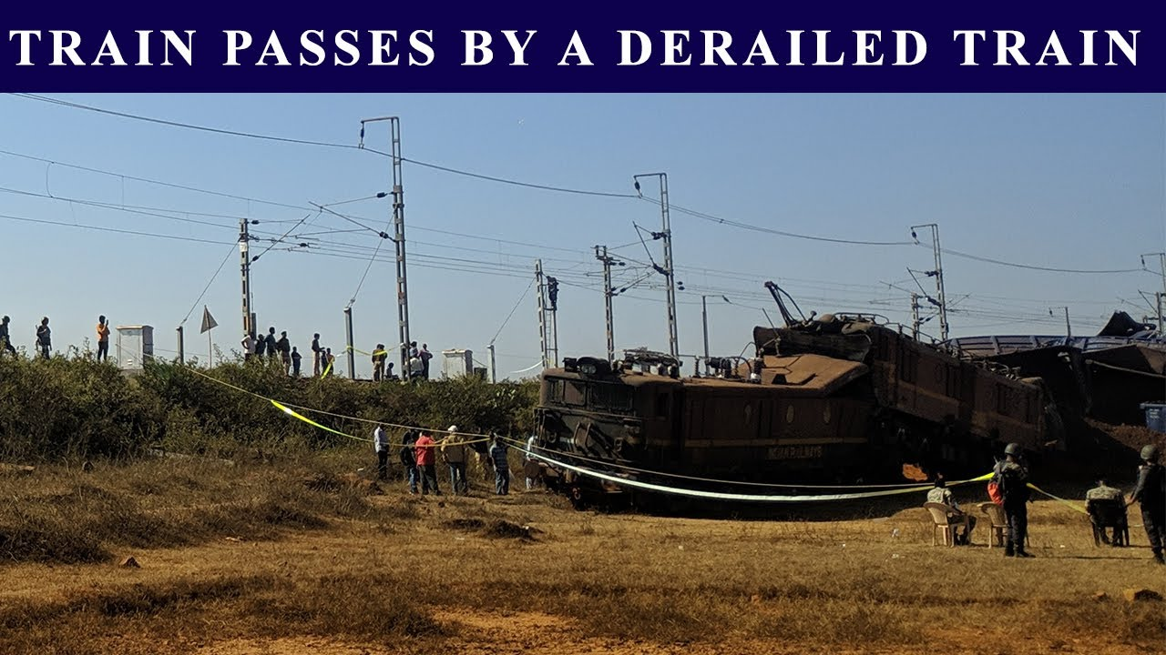 A GOODS TRAIN PASSING BY A DERAILED TRAIN ON THE OTHER LINE HONKING REPEATEDLY  TO ENSURE CLEAR  WAY