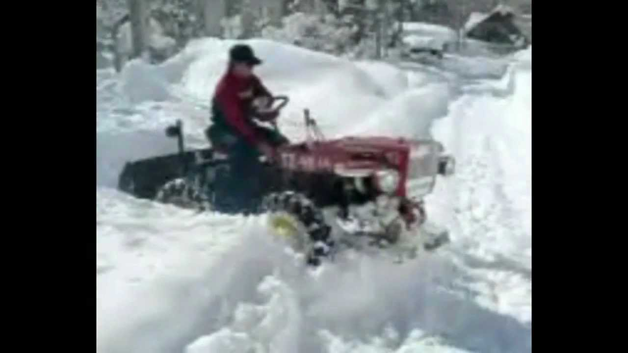 Mini Articulated 4x4 Garden Tractor Plowing Through Snow