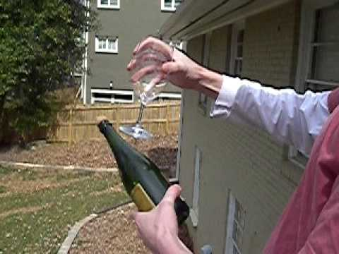 Jon and Justin saber champagne with a wine glass